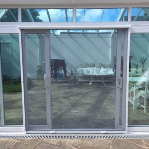 Vertical retractable insect screen door